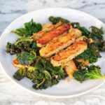 Lemon garlic tempeh slices over a bed of cooked kale.