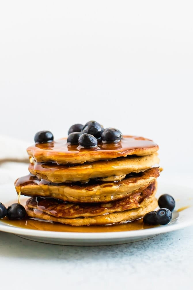 Stack of blueberry protein pancakes drizzled with maple syrup.