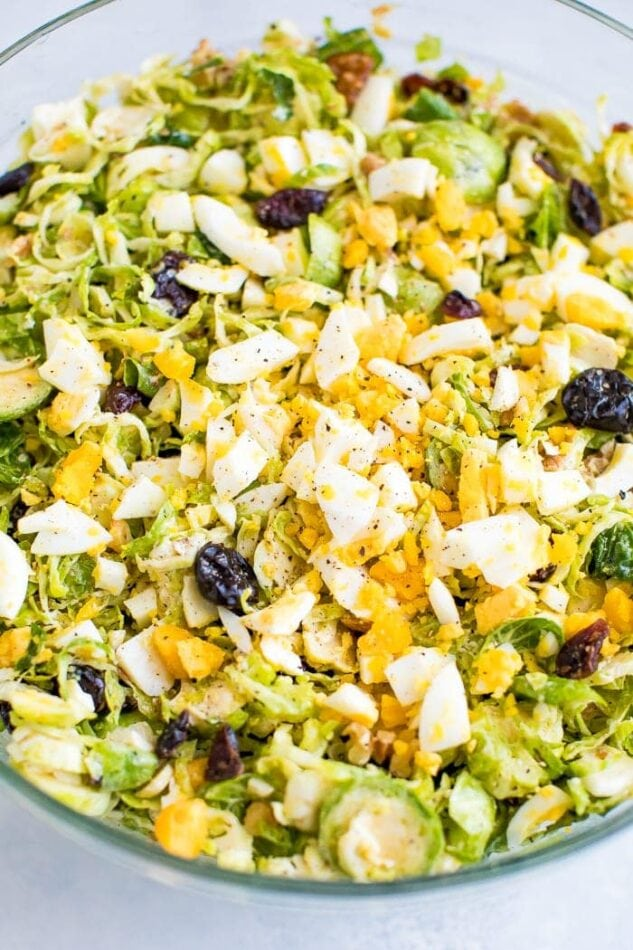 Healthy chopped Brussels sprout salad with feta, walnuts, cranberries, and egg.