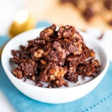 Chocolate granola in a white bowl with milk on a blue napkin.