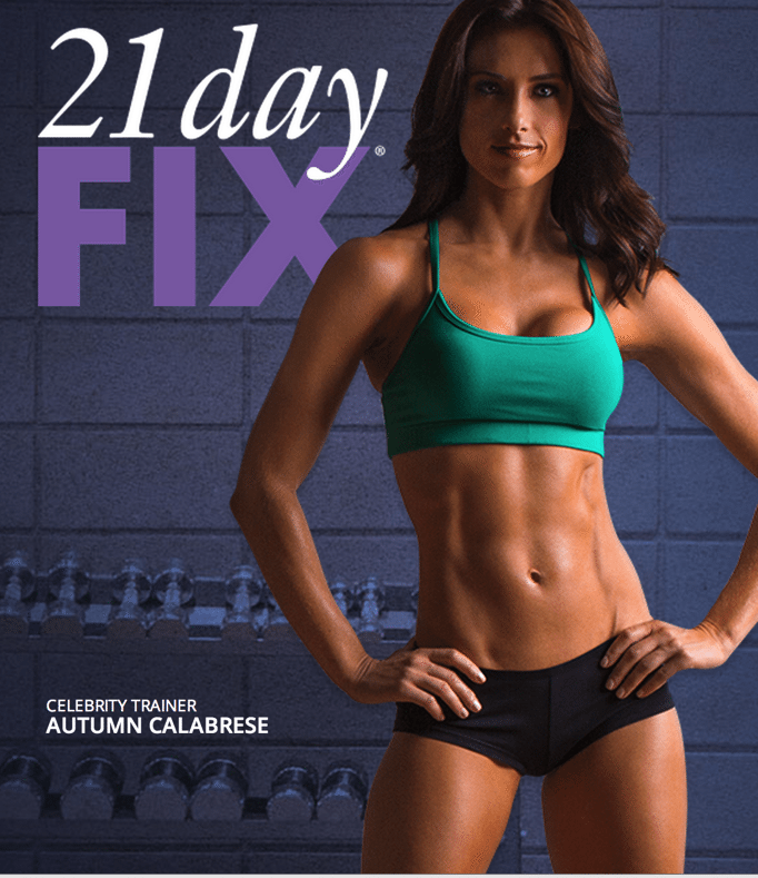 Woman in green sports bra and black shorts standing in front of navy brick wall with text '21 day FIX' on top.