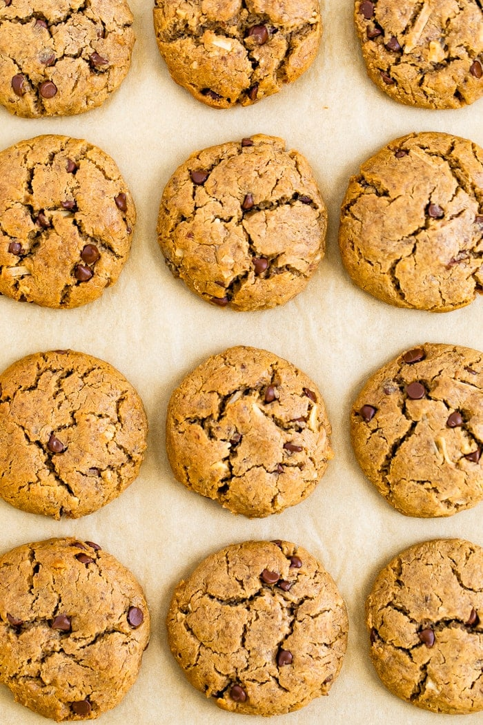 Chocolate chip tahini cookies on a baking sheet lined with parchment paper.