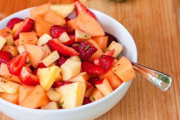 Fresh Fruit Salad with Mint and Maple Syrup served in a white bowl on wood cutting board.
