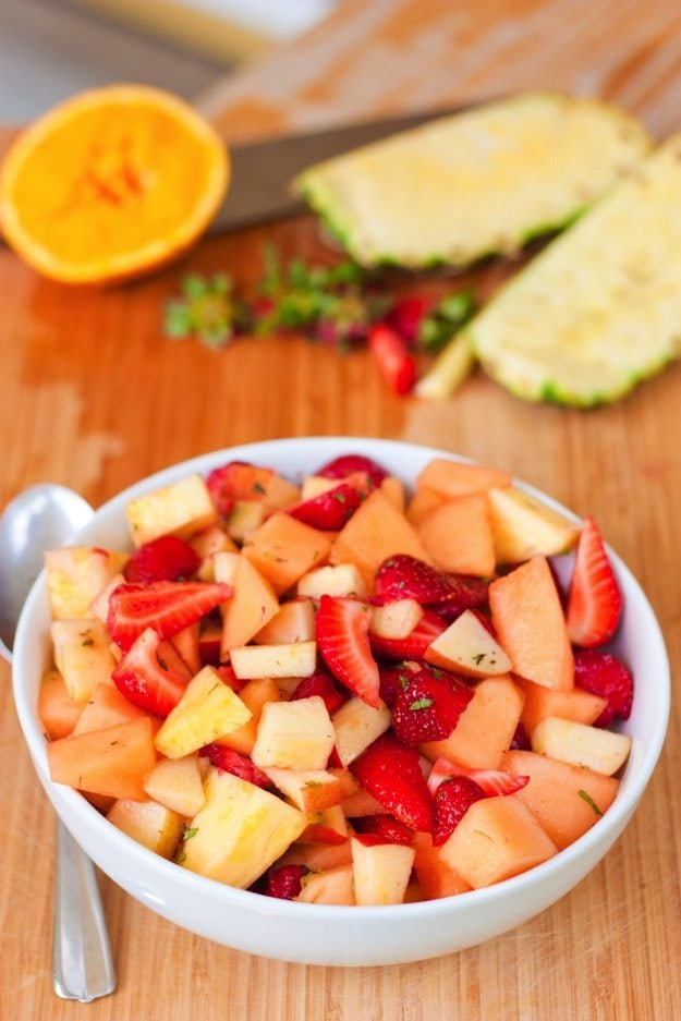 Fresh Fruit Salad with Mint and Maple Syrup served in a white bowl on wood cutting board with chopped fruit.