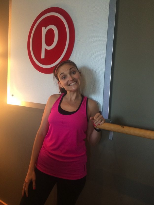 Girl in pink tank top and black pants inside barre studio