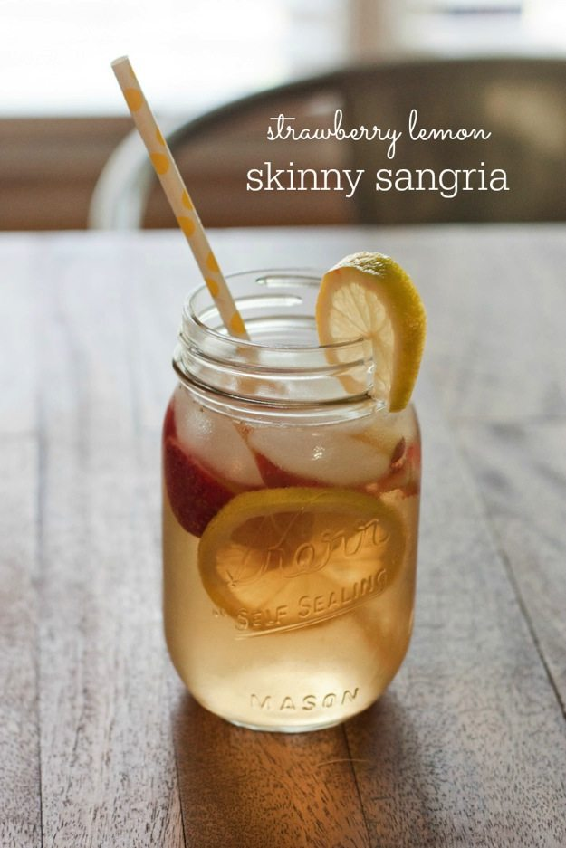 Strawberry Lemon Skinny Sangria in clear mason jar with yellow straw on wood table.
