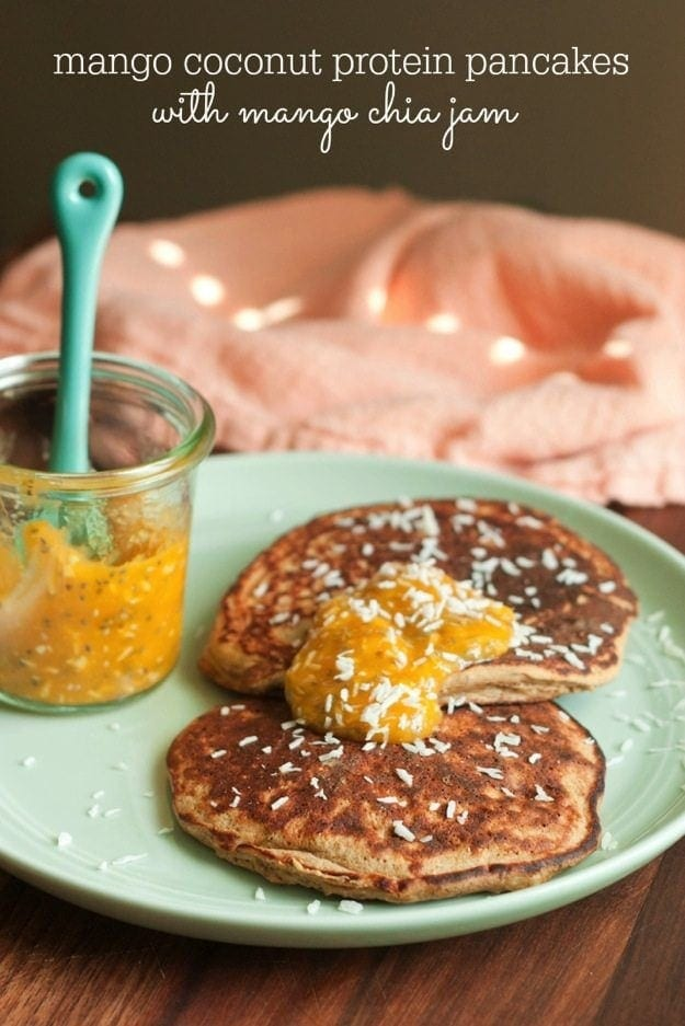 Mango Coconut Protein Pancakes with Mango Coconut Chia Jam on light green plate with jar of chia jam.