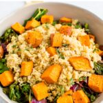 Bowl of kale salad topped with quinoa and roasted sweet potato cubes.