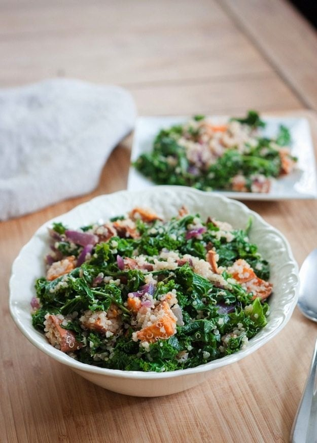 Roasted Sweet Potato, Kale and Quinoa Salad in white serving bowl on light wood cutting board with plate of salad in background.