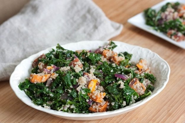 Roasted Sweet Potato, Kale and Quinoa Salad in white serving dish on light wood cutting board.