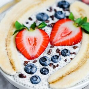 Bowl with chia pudding topped with a split banana, strawberries, blueberries and cacao nibs.