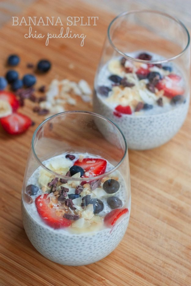 Two glasses filled with banana split chia seed pudding, topped with blueberries, banana slices, strawberries and cacao nibs.