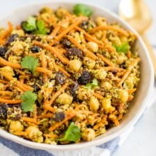 A carrot salad with raisins, quinoa, chickpeas in a bowl with a gold spoon on the right.