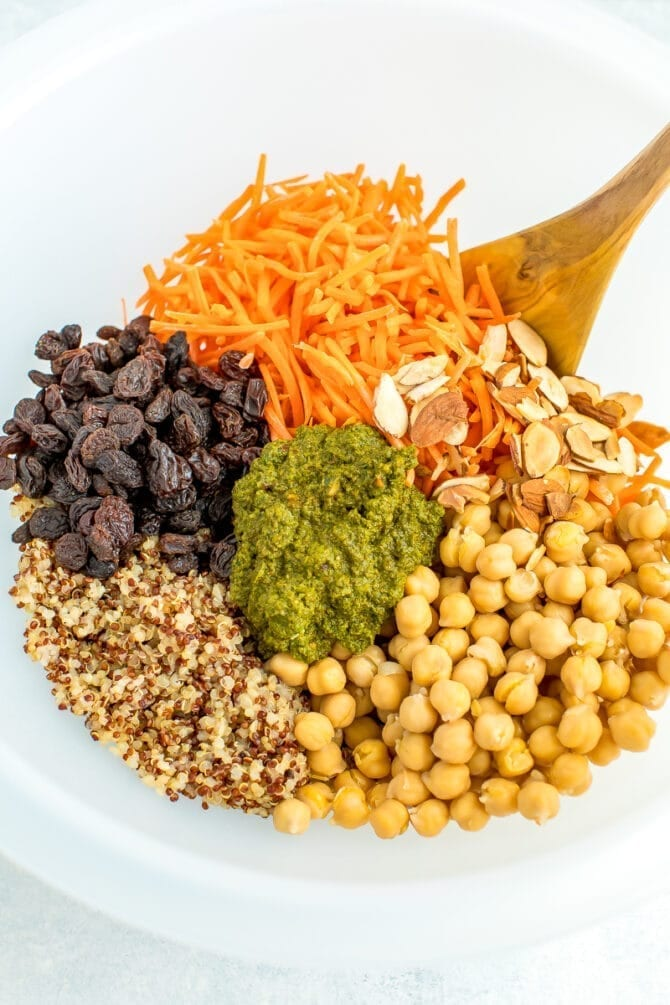 Large bowl with ingredients for a carrot raisin salad including quinoa, chickpeas, carrots, raisins and cilantro almond dressing.