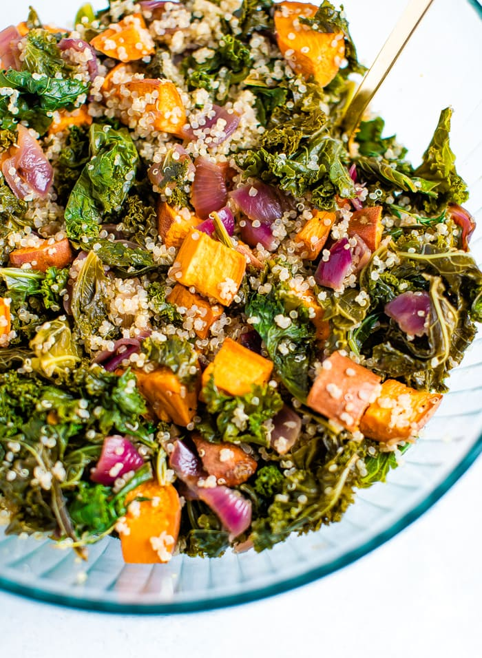 Bowl of tossed kale quinoa sweet potato salad with caramelized onions and fresh herbs.