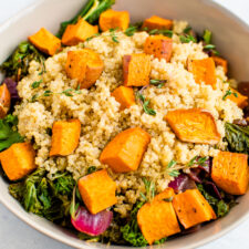 Kale salad with quinoa and roasted sweet potatoes on top.