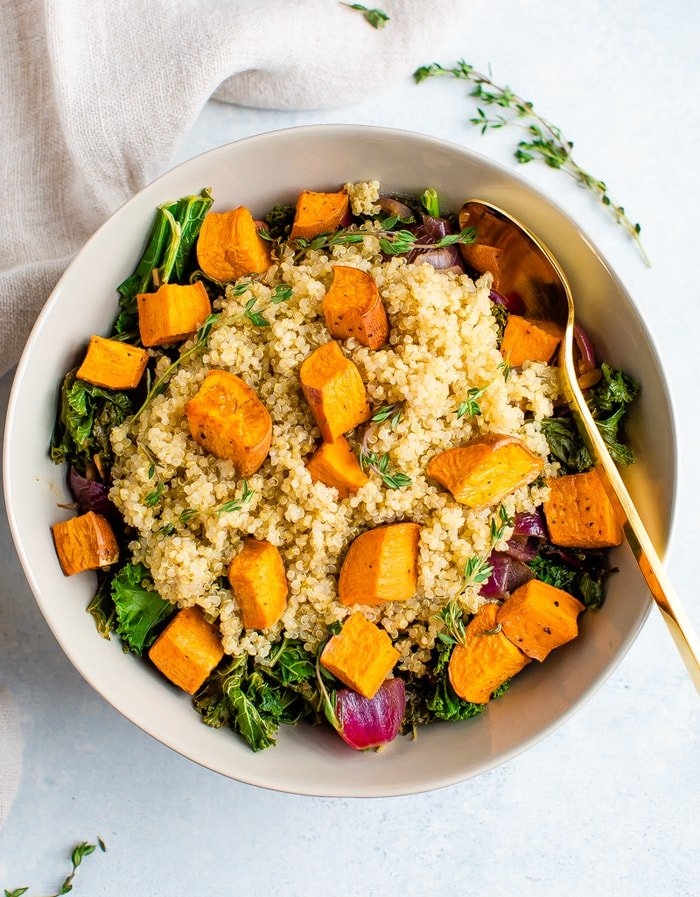 Salad bowl with kale, quinoa and roasted sweet potatoes topped wit fresh thyme.