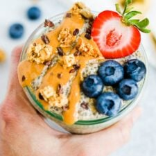 Hand holding a jar of peanut butter chia pudding topped with peanut butter, cacao nibs, granola, a strawberry and blueberries.