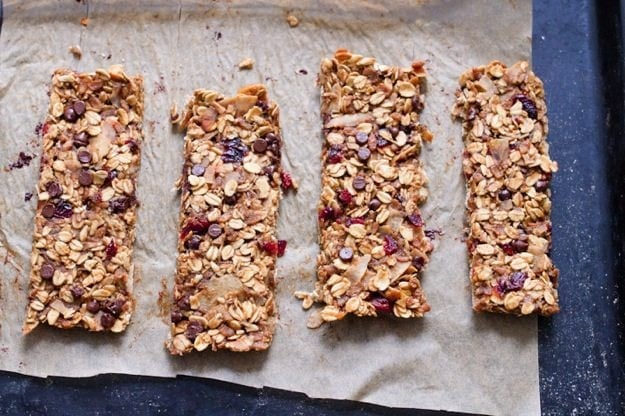 Cranberry Coconut Chocolate Chip Granola Bars on cookie sheet with piece of parchment.