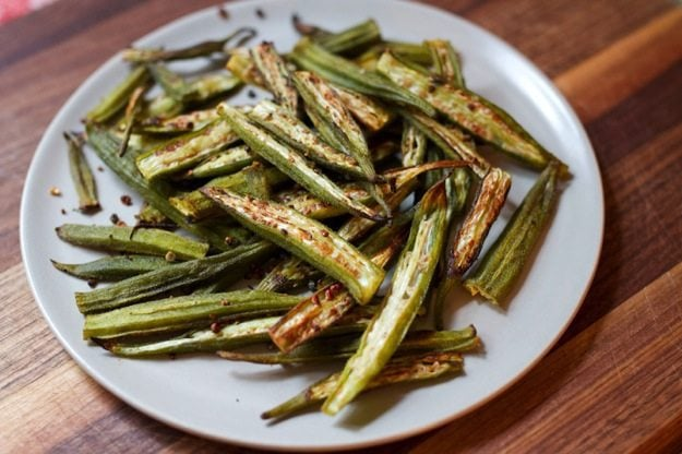 White plate with oven roasted okra sitting on a wood table.