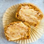 Healthy pumpkin cornbread muffin sliced and laying on a muffin liner and spread with ghee.