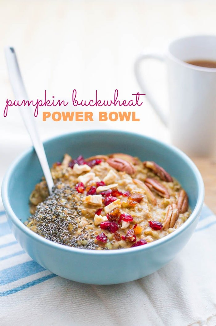 Buckwheat Pumpkin Power Bowl topped with chia seeds, dried cranberries, apples and pecans served in a light blue bowl on white dish towel - cup of coffee in background.