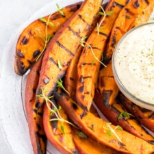 Plate of grilled sweet potato wedges on a plate, topped with fresh herbs. A creamy dipping sauce is to the side.