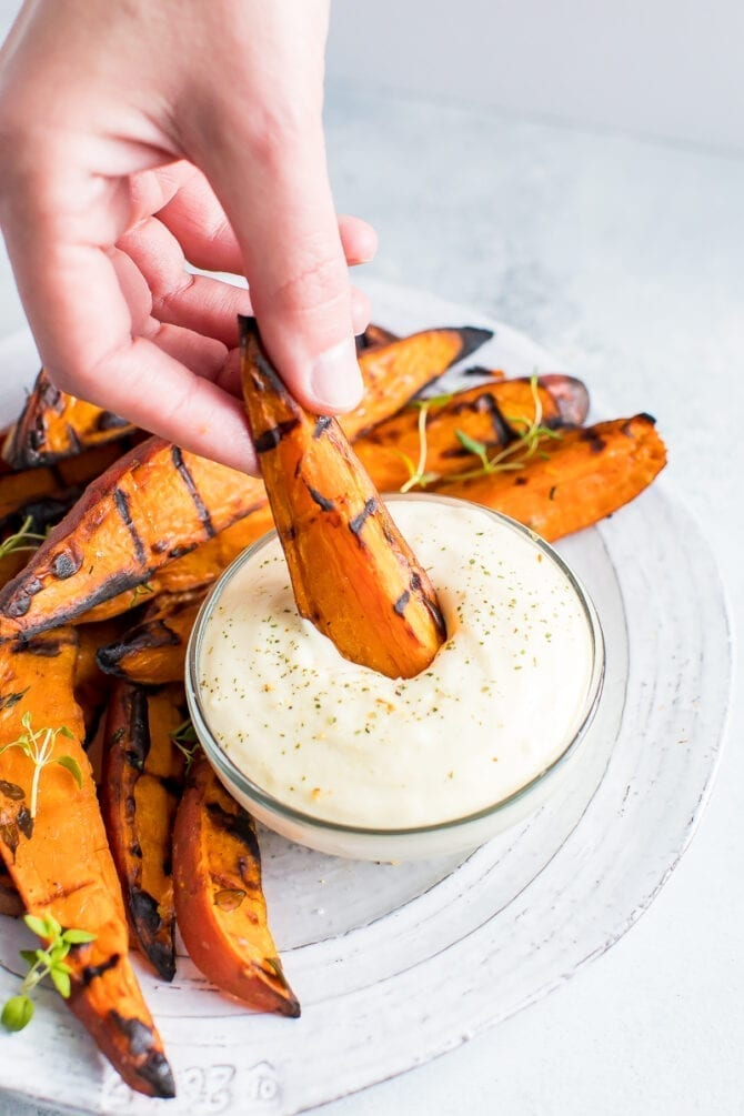 Hand dipping a grilled sweet potato wedge into a bowl of creamy dip.