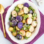 Tri-colored potato salad with shallots and spinach in a white bowl with a purple napkin and gold spoon.