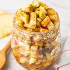 Raw apple pie filling a glass jar.