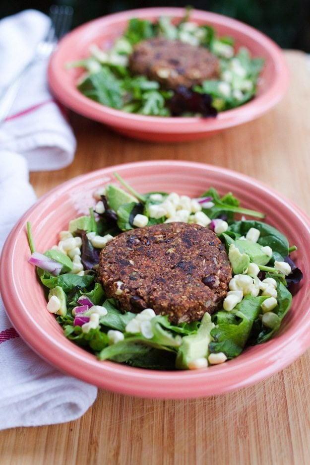 Spicy Chili Black Bean Burger over Salad, served in pink bowls on wood cutting board.