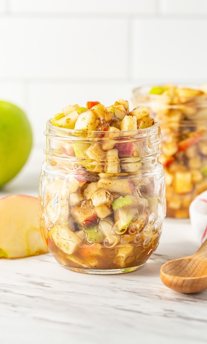 Straight on image of raw apple pie filling a glass jar.