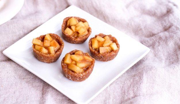 4 raw mini apple pies on a plate.