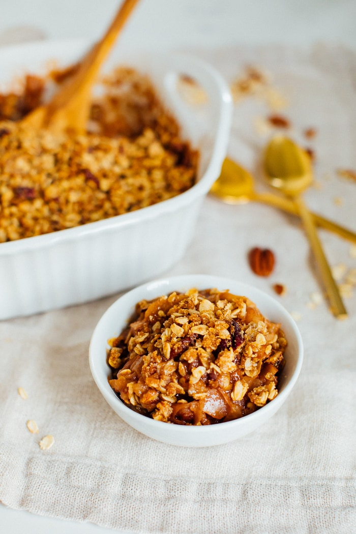 A bowl of apple crisp with oat and pecan topping. The baking dish with a serving spoon is behind the bowl.