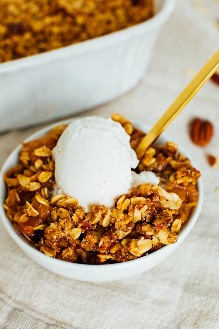 A bowl of apple crisp with oatmeal and pecan topping, topped with vanilla ice cream.