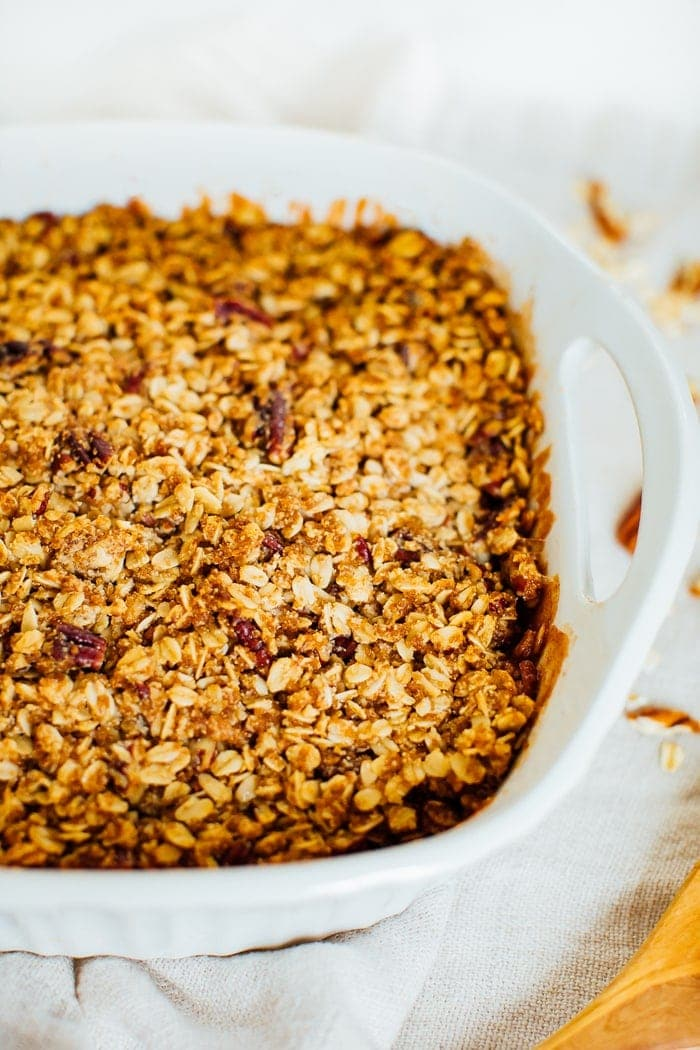 Apple crisp with an oat and pecan topping in a baking dish.