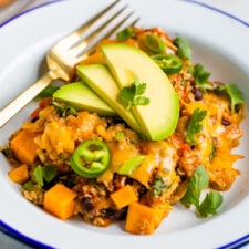 Plate with a cheesy Mexican quinoa casserole topped with jalapenos slices, avocado, and cilantro.