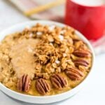 Protein egg white pumpkin oatmeal topped with peanut butter, granola, and pecans.
