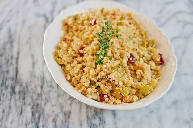 Gluten-Free Thanksgiving Quinoa Stuffing in a white serving dish on a marble countertop.