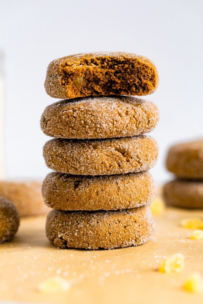 Stack of gingersnap cookies. The top one has a bite taken out of it.