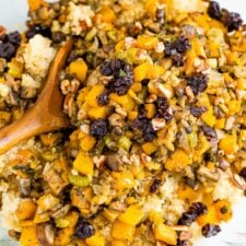 Bowl and wooden spoon with quinoa stuffing made with cranberries and butternut squash.