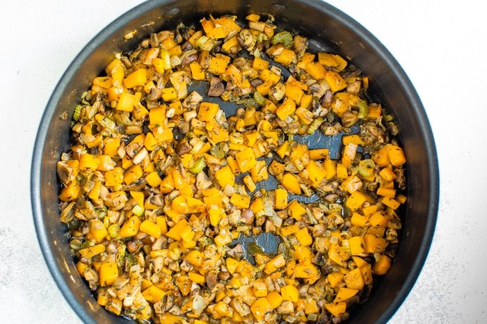Celery and butternut squash being sauteed in a pan.