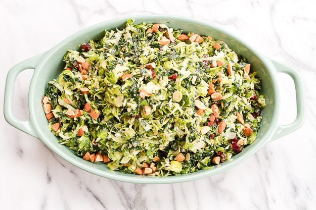 Shredded kale and Brussels sprout salad in an oval serving dish. Salad has cranberries, almonds, onions and cheese tossed in it.