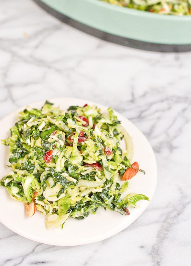 Shredded kale and brussels sprout salad on a plate with the serving dish in the background.