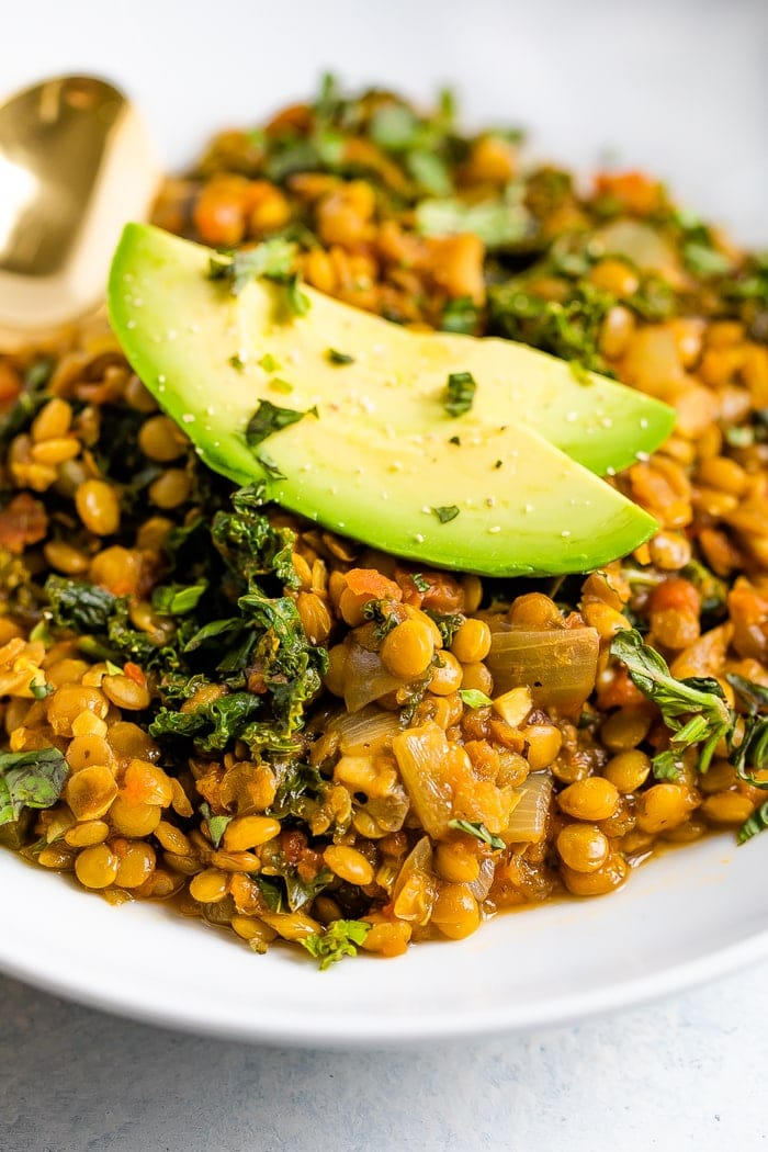 Close up of thick lentil stew with kale and topped with avocado slices.