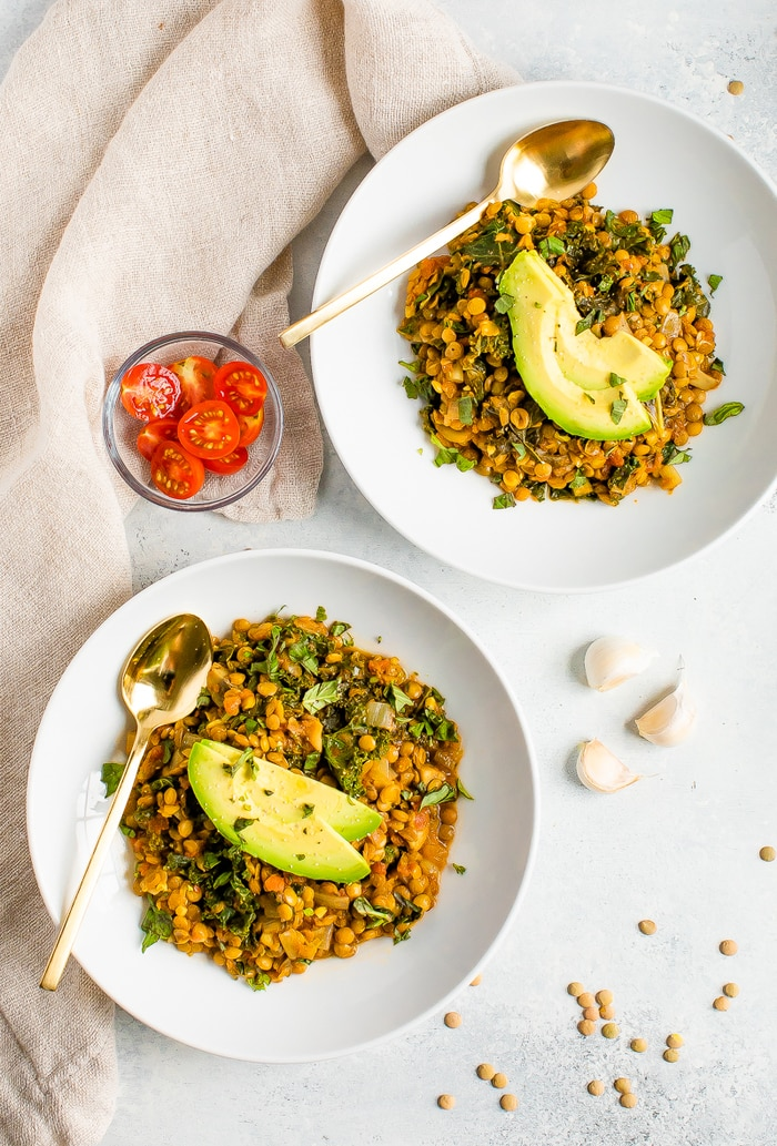 Two bowls of lentil stew with kale and topped with avocado slices. Gold spoons are on the sides of the bowls, and a bowl of cheery tomatoes are around the bowls along with garlic and a cloth napkin.
