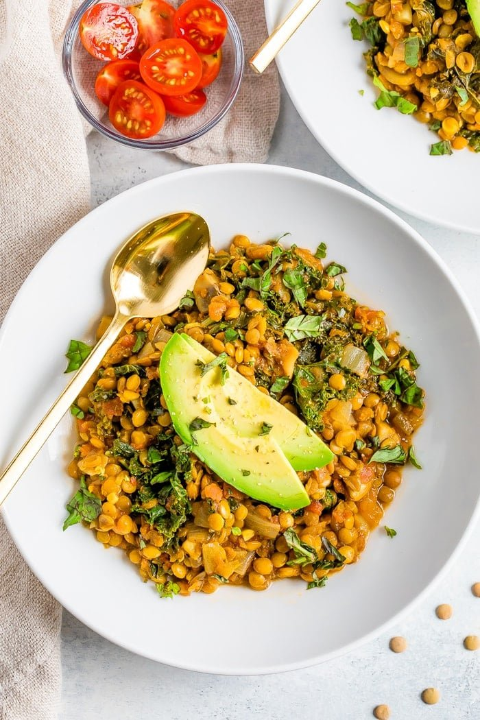 Bowl with lentil stew topped with avocado slices. A gold spoon is on the bowl. A bowl of slices cherry tomatoes is to the side.