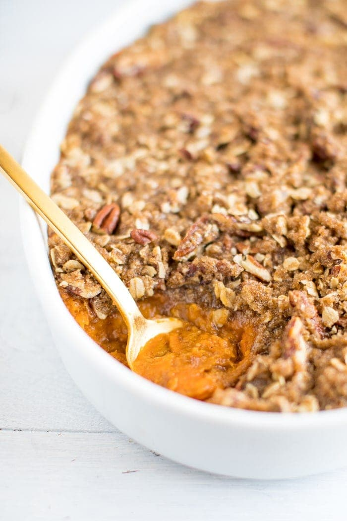 A white baking dish with healthy sweet potato casserole with a gold spoon scooping out a portion.