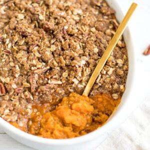Overhead shot of a white baking dish with sweet potato casserole with a gold spoon scooping out a portion.