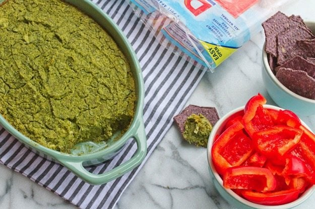 Vegan Spinach Artichoke Dip in light green serving dish next to bowl of chips and sliced red bell peppers.